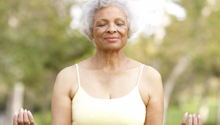 senior woman meditates outside as form of self care