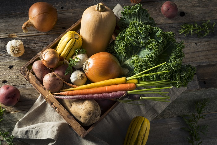 Onions, squash, carrots, and kale in a wooden crate