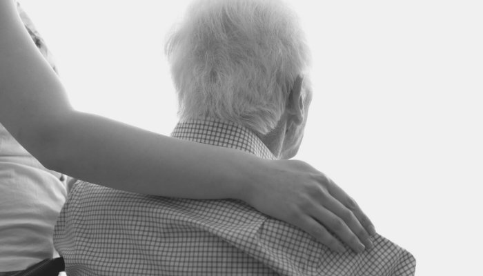 Caregiver comforts senior man with dementia-related aggression