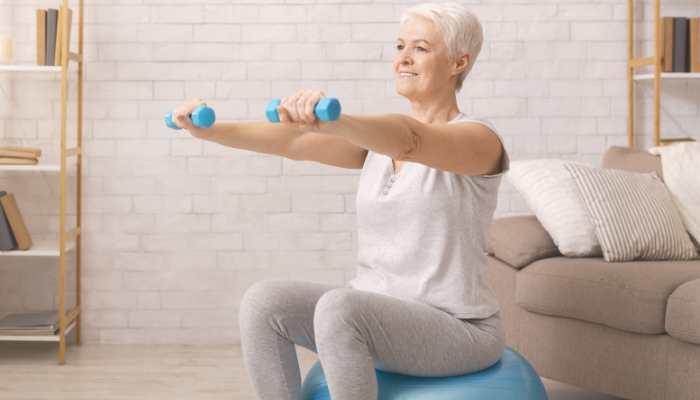 Senior woman working out with dumbbells and stability ball at home in nyc