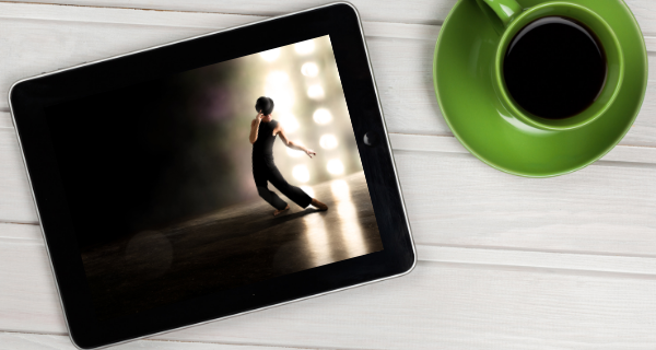 Tablet with Broadway show streaming sitting on desk next to a cup of coffee