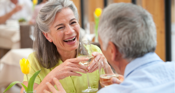Senior couple holding a glass of wine, enjoying dinner outside