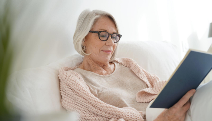 Older woman reads a classic novel in bed before watching the movie adaptation