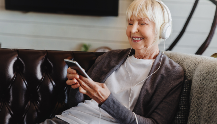 Older woman wears headphones listening to a wellness podcast on her phone while sitting on the couch.